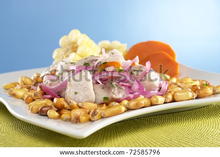 Peruvian ceviche made out of raw mahi-mahi fish (Spanish: perico), onions and aji (hot pepper) and served with roasted corn (cancha) and cooked corn and sweet potato (Selective Focus, Focus on front) - stock photo