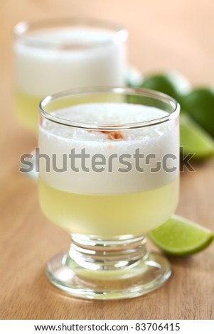 Peruvian cocktail called Pisco Sour made of Pisco (Peruvian grape schnaps), lime juice, syrup and egg white (Selective Focus, Focus on the front glass rim) - stock photo