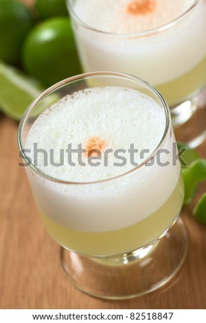 Peruvian cocktail called Pisco Sour made of Pisco (Peruvian grape schnaps), lime juice, syrup, egg white, and some angostura bitter drops on top (Selective Focus, Focus on the middle of the angostura)