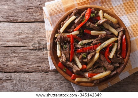 Peruvian cuisine: Lomo saltado on a plate. horizontal view from above, rustic