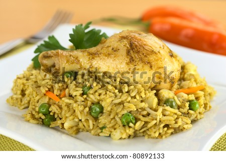 Peruvian dish called Arroz con Pollo, which is made of rice, chicken parts, peas, corn, aji (hot pepper), cilantro (Selective Focus, Focus on the right front part of the chicken thigh) - stock photo