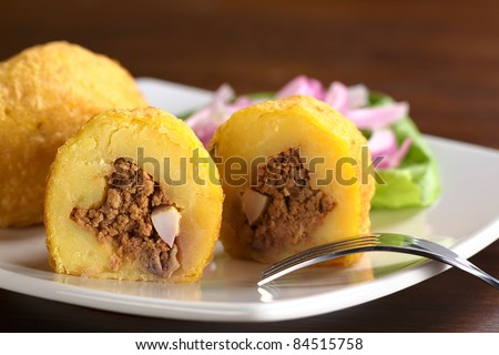 Peruvian dish called Papa Rellena (Stuffed Potato) made of mashed potatoes and filled with meat and egg (Selective Focus, Focus on the front of the half papa rellena) - stock photo