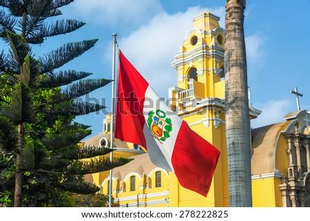 Peruvian flag and yellow church in the Barranco neighborhood in Lima, Peru - stock photo