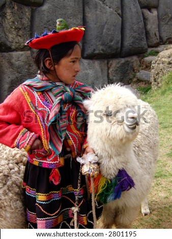 Peruvian girl in traditional dress with bird and lama at ruins near Cusco.