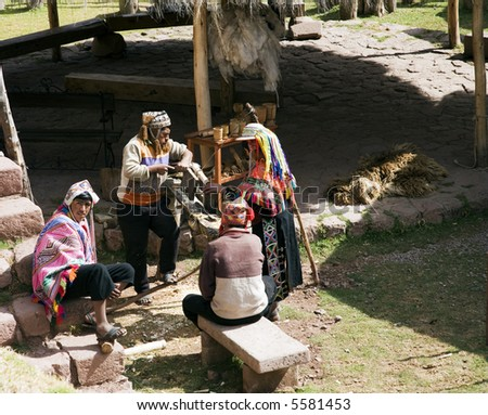 Peruvian Men and Women in Traditional Dress at Weaving Center - stock photo