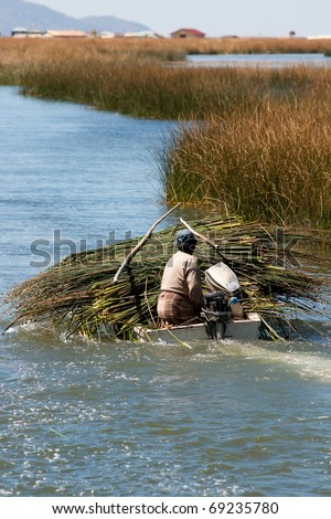 Peruvian peasant floating on a boat among the thickets of reeds on Lake Titicaca - stock photo