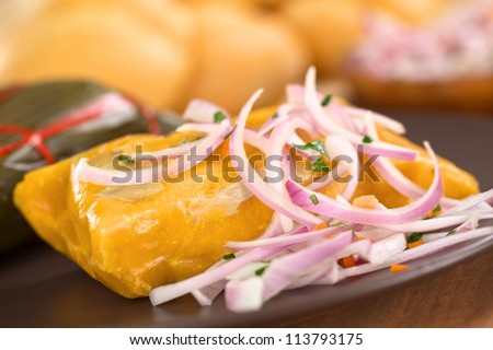 Peruvian tamale (traditionally eaten for breakfast on Sundays) made of corn and chicken and served with salsa criolla (onion salad) (Selective Focus, Focus one third into the tamale) - stock photo