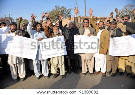 PESHAWAR, PAKISTAN - DEC 22: Members of WAPDA Hydro Electric Central Labor Union shout slogans in favor of their demands during a protest demonstration at Peshawar press club on December 22, 2011. - stock photo
