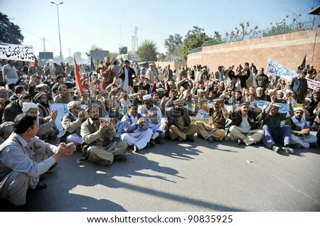 PESHAWAR, PAKISTAN - DEC 14: Supporters of WAPDA Hydro Electric Central Labor Union shout slogans in favor of their demands during protest demonstration at Governor House on December 14, 2011 in Peshawar, Pakistan. - stock photo
