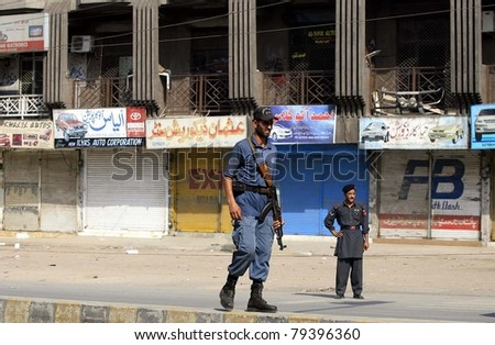 PESHAWAR, PAKISTAN - JUN 16: Security officials stand alert while the shops are closed due to the threats of terrorism, at FC roundabout on  June 16, 2011 in Peshawar. - stock photo
