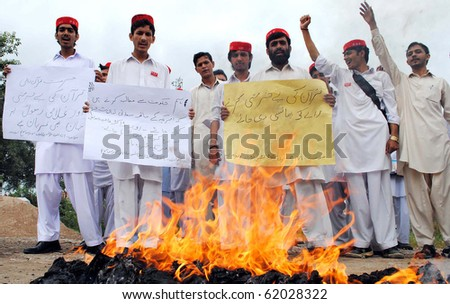 PESHAWAR-SEPT 29:Activists of Azad Pakhtoon Students Federation stand near burning tyres as they protest against desecration of the Holy Quran in US & for the release of Aafia Sept 29,2010 in Peshawar