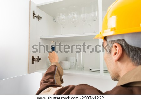 Pest Control Worker With Flashlight Checking Kitchen Shelf - stock photo