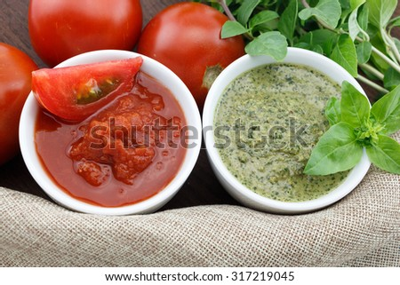Pesto and tomato sauce with fresh basil leaves and tomatoes - stock photo