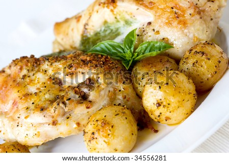 pesto chicken breasts with baby potatoes on white plate - stock photo