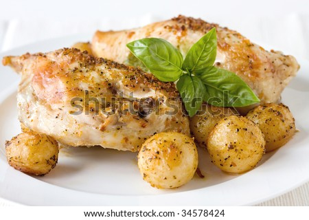 pesto chicken breasts with potatoes on the white plate - stock photo