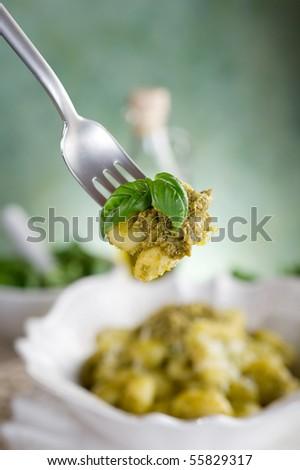 pesto gnocchi over fork - stock photo