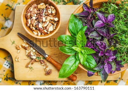 Pesto ingredients on a cutting board, shallow dof - stock photo