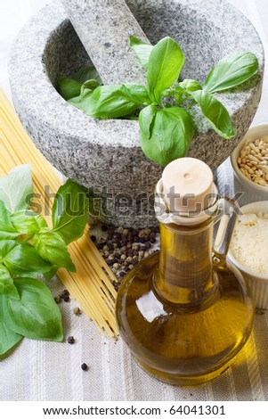 Pesto ingredients; spaghetti pasta, olive, parmesan, pepper grain, basil, and pine nuts. Still life with mortar