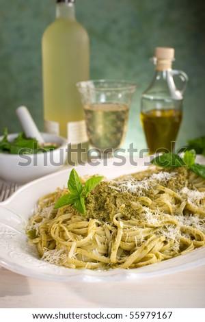 pesto pasta on dish with white wine - stock photo