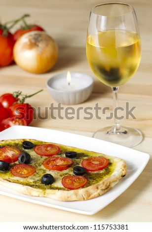Pesto pizza with tomatoes and black olives on a white plate