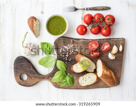 Pesto sauce, bread, cherry-tomatoes, fresh basil and garlic on rustic walnut chopping board over white wooden backdrop, top view - stock photo
