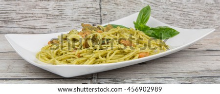 Pesto spaghetti with shrimps and squids in white plate over wooden background