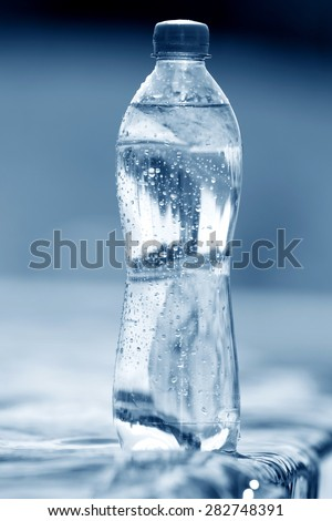 PET bottle with water on a water surface background - stock photo