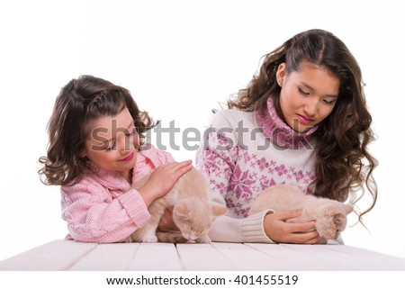 Pet love is shown because of loving faces of children holding their ginger kittens on wooden table on white background. Asian and Caucasian appearances of girls. Beautiful kids with lovely felines. - stock photo