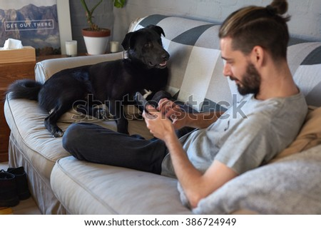 Pet owner hanging out with his dog on the couch sofa, while surfing the internet on his tablet device
