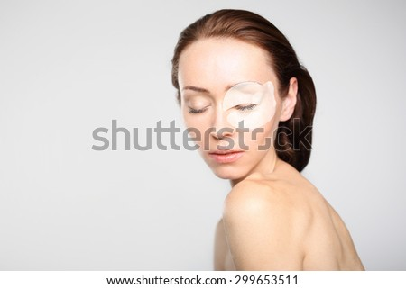 Petal collagen eye, a way to smooth skin. Portrait of a beautiful young woman with collagen mask around the eye  - stock photo