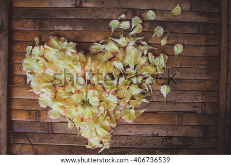 petals flowers hart frame   with a lot of copy space  on brown wood board  background in rustic style for wedding decoration