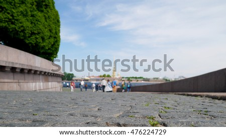 Peter and Paul Fortress across Neva river with Vasilievsky island ramp stone pavement close up, St Petersburg, Russia