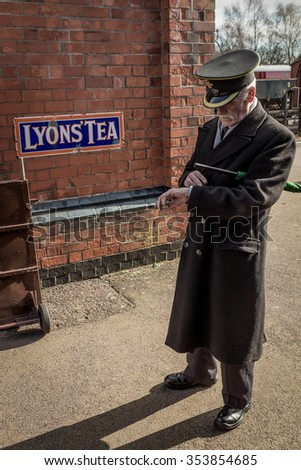 PETERBOROUGH, UK - FEB 22, 2014:Train guard checks his watch on platform at the Great Central Railway
