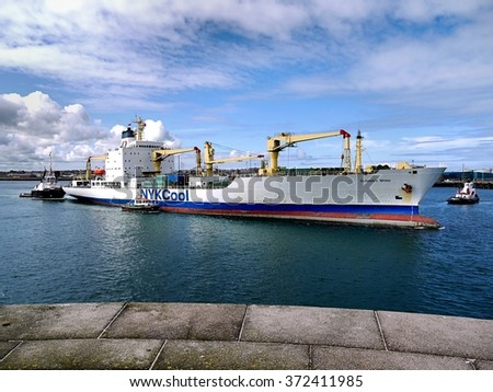 "Peterhead, Scotland, 11th of June 2012, Cargo Ship ""Summer Wind"" leaving harbor assisted by tugboats. - stock photo"