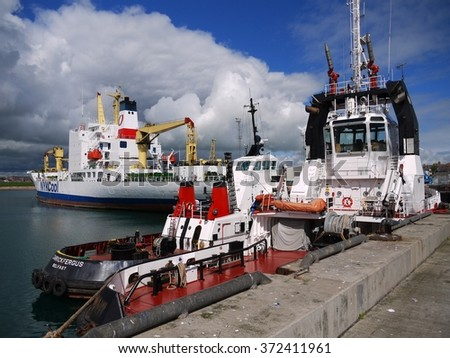 Peterhead, Scotland, 11th of June 2012, Harbor Tugs on standby for towing operations of cargo ship in port. - stock photo