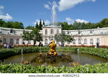 "PETERHOF, RUSSIA - JULY 24, 2015: The ""Triton Who Is Breaking Off a Mouth to a Sea Monster"" fountain against the Big greenhouse in Nizhny park"