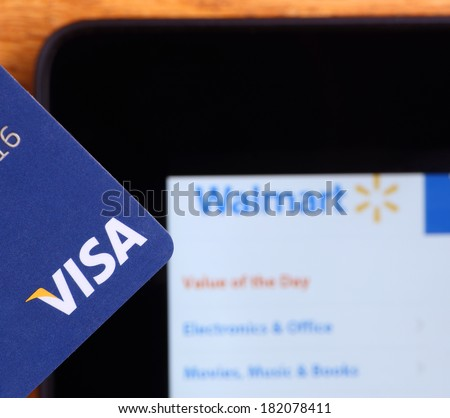 PETERSBURG, ILLINOIS-MARCH 8, 2014:  Closeup of a Visa credit card with a tablet showing Walmart's web site in background. Visa, Inc. is an American financial services corporation.