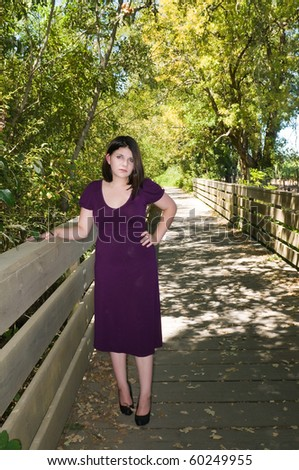 Petite young brunette on a wooden footbridge