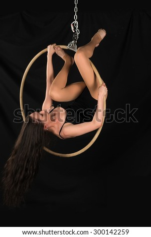 Petite young brunette on an aerial ring - stock photo