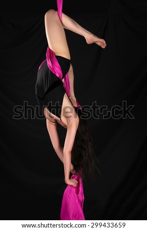 Petite young brunette suspended from a purple fabric - stock photo