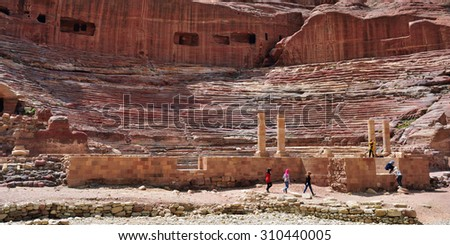 PETRA, JORDAN - APR 1, 2015: Tourists visit the  Petra's ancient amphitheater.Temples, tombs, theaters and other buildings are scattered over 400 square miles