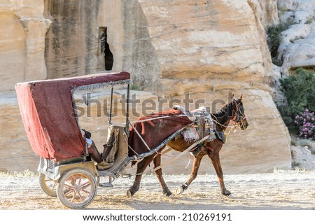 PETRA, JORDAN - APR 29, 2014: Unidentified tourists in a horse carriage in Petra, Jordan. Petra is one of the New Seven Wonders of the World.