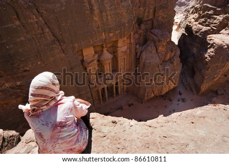 PETRA, JORDAN - JULY 14: Unidentified Bedouin womans looks down the  Treasury Temple at Petra (Al Khazneh)  on July 14, 2009 in Petra, Jordan. Al Khazneh is carved out of solid sandstone rock. - stock photo