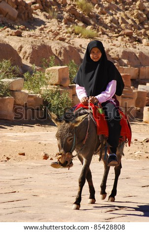 PETRA, JORDAN - NOVEMBER 25: Unidentified Bedouin woman rides through the ruins of ancient Petra on November 25, 2009 in Petra, Jordan. Petra is a UNESCO World Heritage Site since 1985. - stock photo