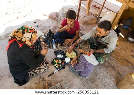 PETRA,  JORDAN - OCT 12, 2014: A family who sells tourists souvenirs in Petra in Jordan is sitting on the ground while they eat - stock photo