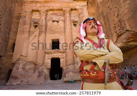 PETRA,  JORDAN - OCT 12, 2014: A guard in ancient costume in front of one of the royal tombs in Petra in Jordan - stock photo