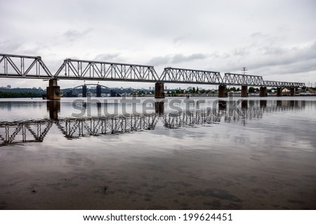 Petrivskiy railroad bridge in Kyiv (Ukraine) across the Dnieper shot from the left bank of the river on the cloudy day, - stock photo