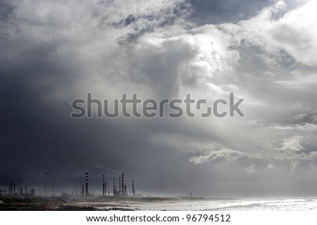 Petro-chemical refinery under an heavy stormy sky.