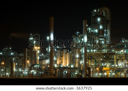 Petrochemical industry, showing stainless steel tubes and pipes at night - stock photo
