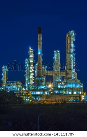 Petrochemical plant at night with reflection on water  - stock photo